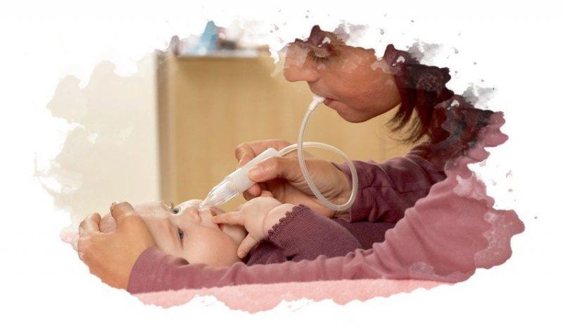 мать прочищает нос ребенку