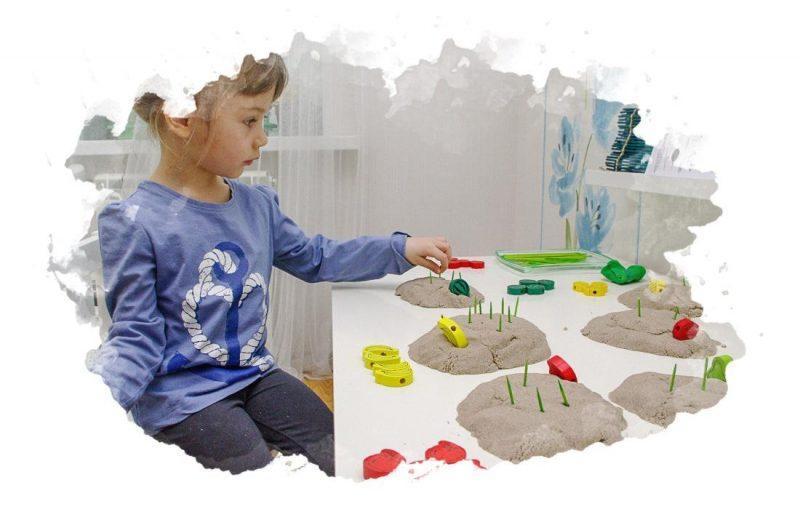 девочка играет в кинетический песок