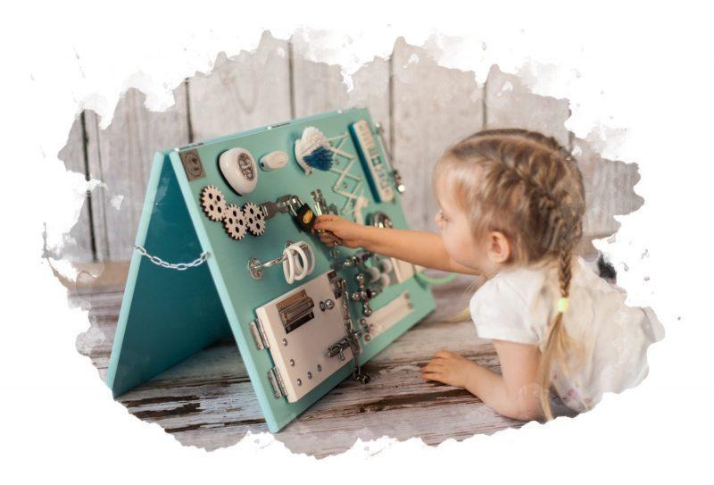 ребенок играет с бизибордом